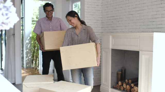 Couple carrying moving boxes into their new home