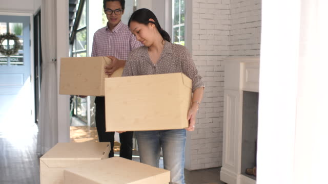 couple carrying moving boxes into their new house - carrying stock videos & royalty-free footage