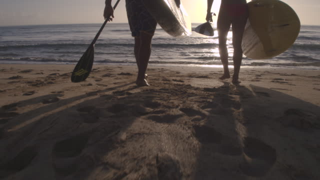 Couple carrying their paddle boards down to the water