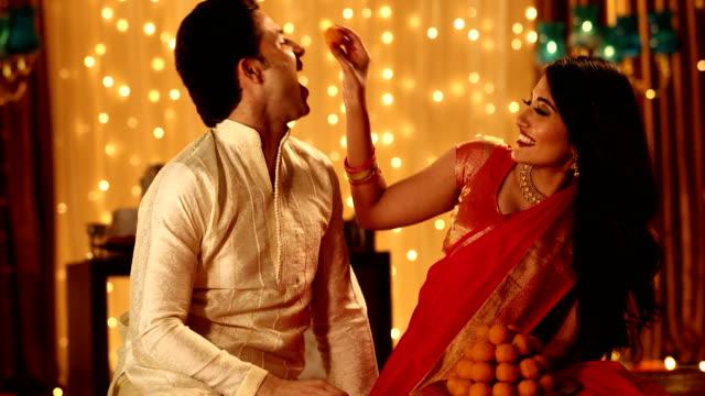 couple celebrating diwali festival, delhi, india - sweet food stock videos & royalty-free footage