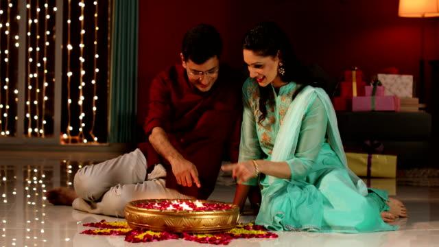 couple celebrating diwali festival, delhi, india - 床に座る点の映像素材/bロール