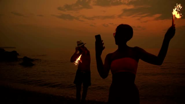SLO MO Couple celebrating with sparklers on the beach