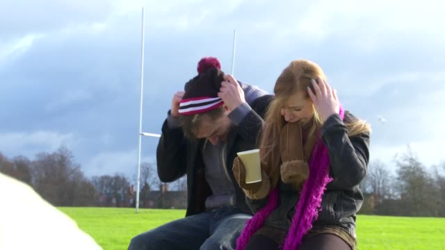 a couple chat with coffee in the park in winter wide shot - mitten stock videos and b-roll footage