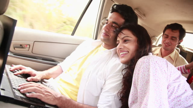 Couple chatting on a laptop in a car