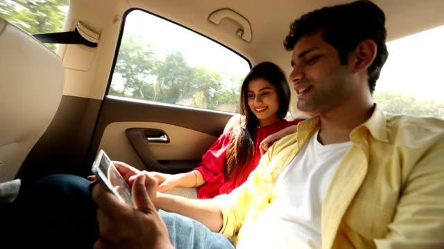 couple chatting on digital tablet in the car, delhi, india - sedile del passeggero video stock e b–roll