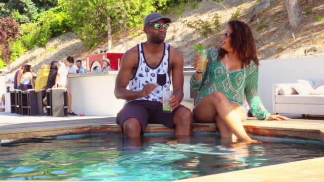 couple chatting on edge of water at pool party - hot tub stock videos and b-roll footage