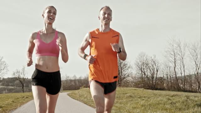 slo mo-ts paar chatten während joggen an einem sonnigen tag - mittlerer teil stock-videos und b-roll-filmmaterial
