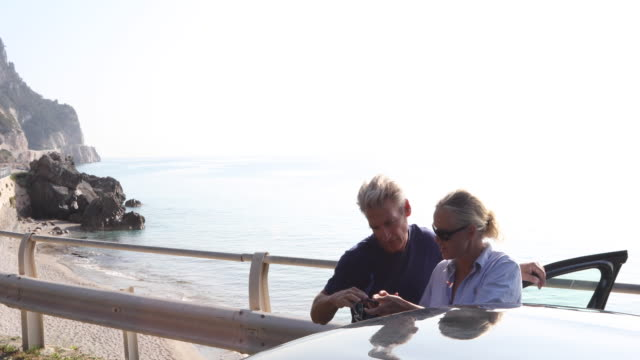 couple check smart phone for direction, coastline road - see other clips from this shoot 56 stock videos & royalty-free footage