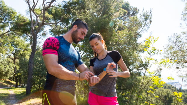 WS couple checking exercise results on smartwatch and fitness tracker