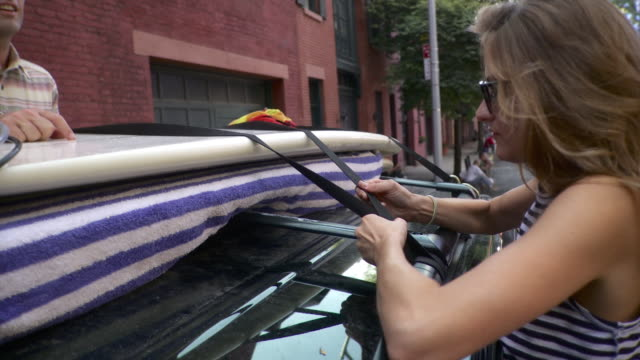 MS PAN Couple checking strapped surfboards onto mini van's roof rack / Brooklyn, New York City, New York State, USA