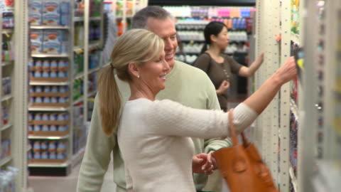 ms pan selective focus couple choosing juice shopping in supermarket, richmond,  virginia, usa - kall dryck bildbanksvideor och videomaterial från bakom kulisserna