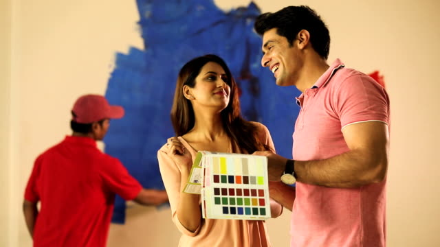 Couple choosing wall colour from color swatch, Delhi, India