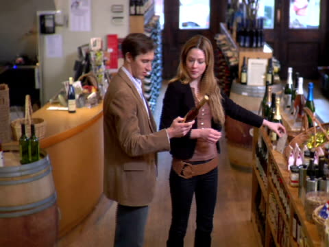 ms, ha, couple choosing wine in liquor store, soho, new york city, new york, usa - hand an der hüfte stock-videos und b-roll-filmmaterial