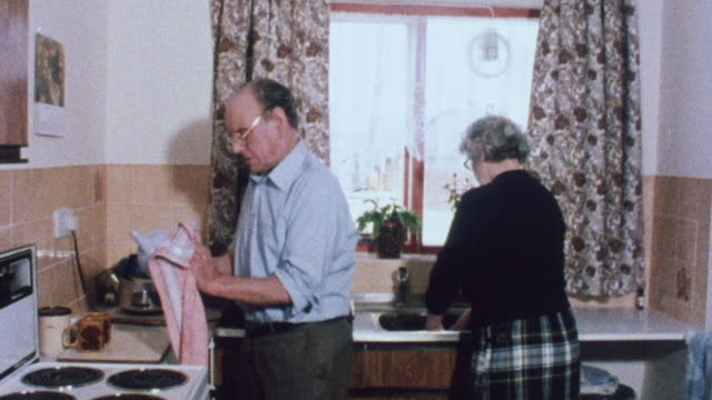 1983 montage couple cleaning the kitchen in their home, lamp being switched off, and wide doorway into bedroom / lowestoft, england, united kingdom - ローストフト点の映像素材/bロール