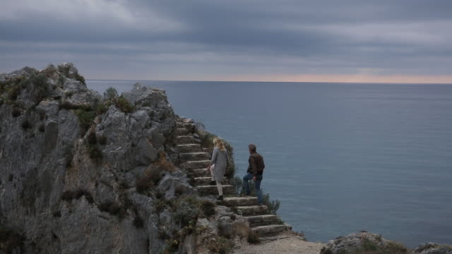 couple climb stone steps above sea, then look out - tunic stock videos & royalty-free footage