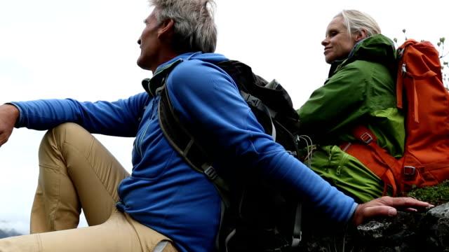 couple climbing above a mountain vista - adventure stock videos & royalty-free footage