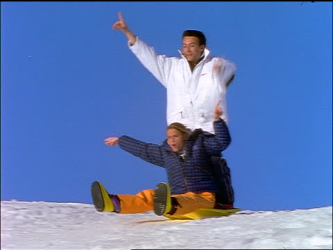 couple coming down hill on sled / man stands up + falls off - paar mittleren alters stock-videos und b-roll-filmmaterial