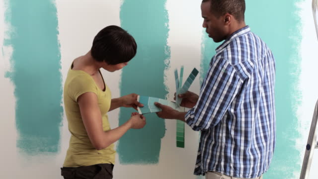stockvideo's en b-roll-footage met couple comparing color swatches with paint on wall - staal