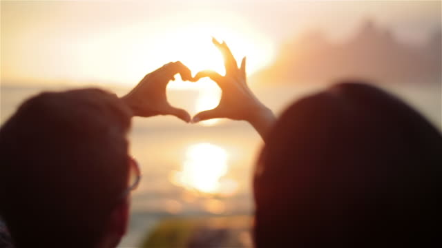 Couple connect hands to make heart shape at sunset on the beach at Ipanema