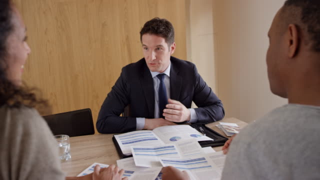 Couple consulting with a personal banker in their home