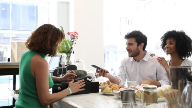 vídeos y material grabado en eventos de stock de pareja contacto menos pago con teléfono inteligente en la cafetería - pago por móvil