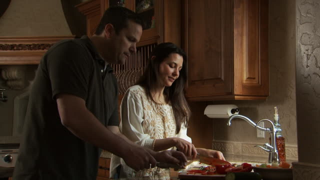 couple cooking in kitchen and smiling - see other clips from this shoot 1167 stock videos and b-roll footage