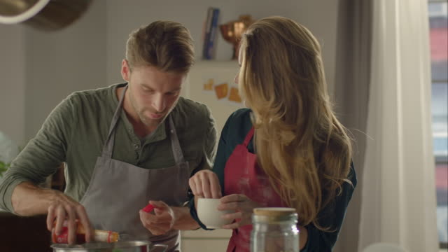 stockvideo's en b-roll-footage met couple cooking together in kitchen and tasting food - pret