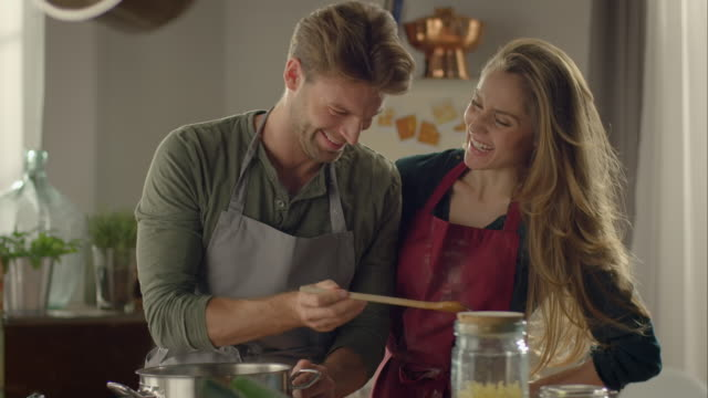 couple cooking together in kitchen and tasting food - apron stock videos & royalty-free footage