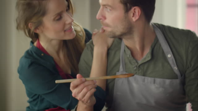 stockvideo's en b-roll-footage met couple cooking together in kitchen - proeven