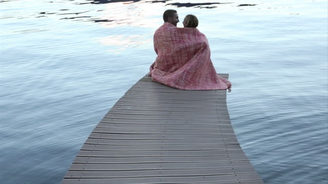 Couple cosy in blanket at end of curving dock