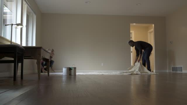 vídeos de stock e filmes b-roll de couple covering floor of new home with dust sheet. - pano de protecção
