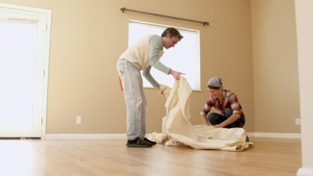 vídeos de stock e filmes b-roll de couple covering floor of room with dust sheet, low angle view. - pano de protecção