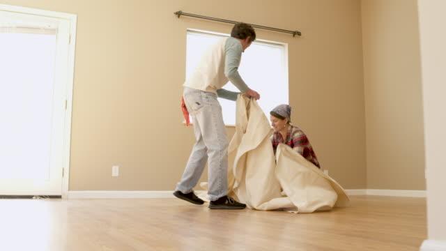 vídeos de stock e filmes b-roll de couple covering floor of room with dust sheet. - pano de protecção