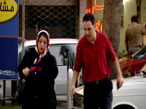 vidéos et rushes de couple crossing busy street, pausing to talk before continuing across / tehran, iran - format vignette