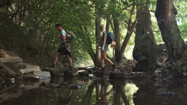 couple crossing river in forest - stepping stone stock videos & royalty-free footage