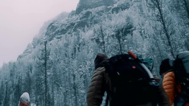 vidéos et rushes de couples traversant la rivière dans les montagnes. marcher sur un pont - tronc d'arbre