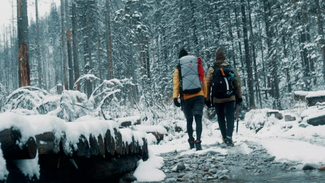 couple crossing the river in mountains. winter trip - stream stock videos & royalty-free footage