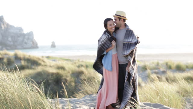 Couple cuddle under blanket, at beach