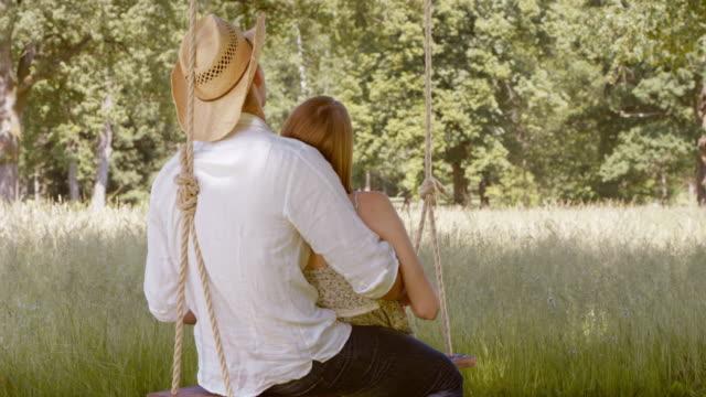 vídeos de stock, filmes e b-roll de slo mo casal cuddling em um balanço no meadow - 18 19 anos