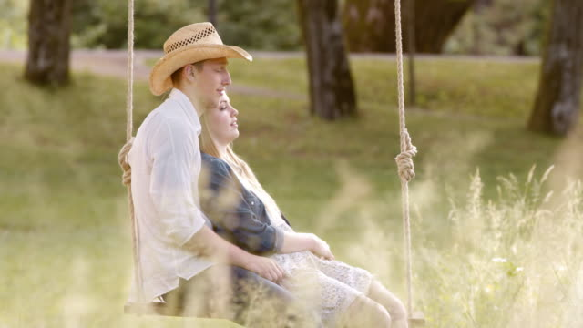 SLO MO DS Couple cuddling on a swing in nature