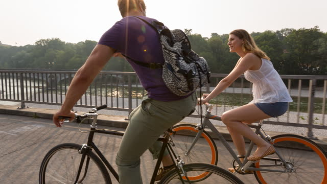 Couple cycling along river