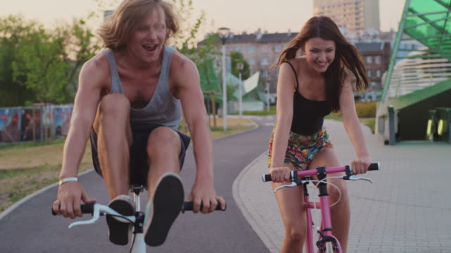 Couple cycling along urban street together
