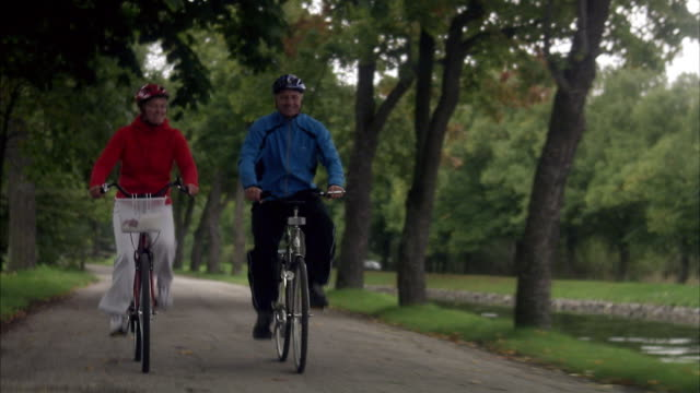couple cycling alongside a canal, sweden. - cycling helmet stock videos & royalty-free footage