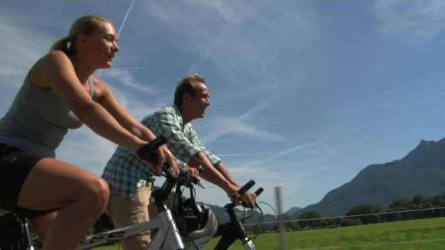 ms la couple cycling in alpine landscape, bavaria, germany - tre quarti video stock e b–roll