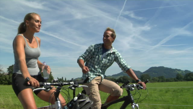 MS Couple cycling in Alpine landscape, Bavaria, Germany