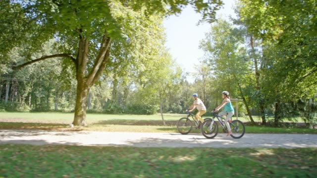 ts couple cycling in the park through an avenue of trees in sunshine - lush stock videos & royalty-free footage