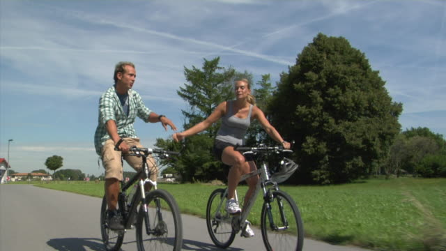 WS DS Couple cycling on rural road, Bavaria, Germany
