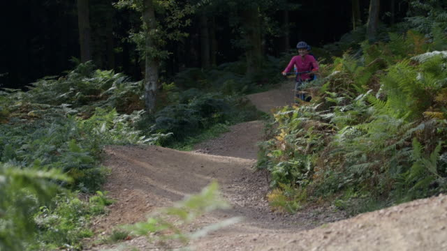 couple cycling on uneven forest track - hill stock videos & royalty-free footage