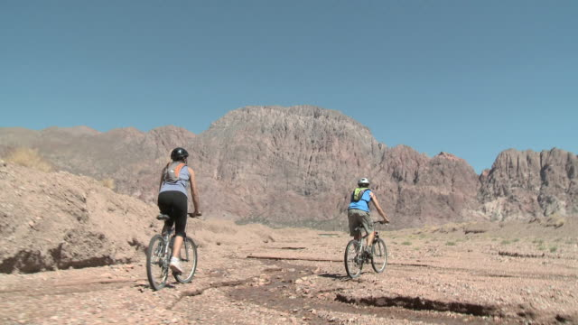 vídeos y material grabado en eventos de stock de couple cycling over rocky landscape - argentina