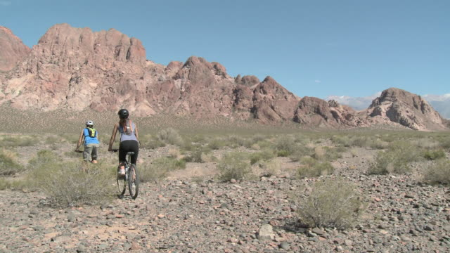 Couple cycling past camera and into distance of rocky landscape